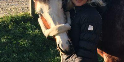 Frau mit blonden Haaren und Pferd mit blauen Augen